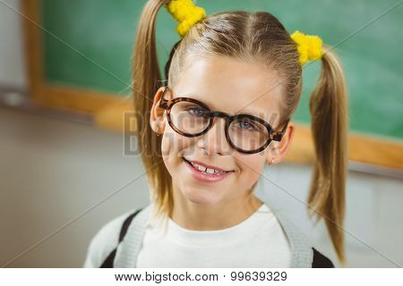 Portrait of cute pupil smiling to camera in a classroom in school