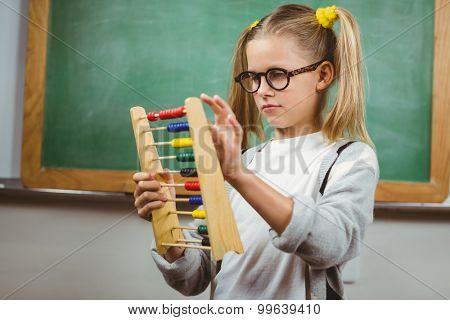 Cute pupil calculating with abacus in a classroom in school