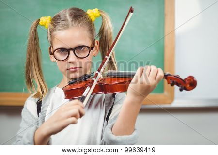 Portrait of cute pupil playing violin in a classroom in school