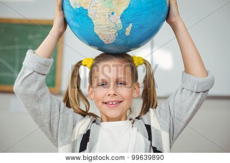 Portrait of cute pupil balancing globe on head in a classroom in school