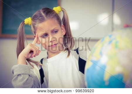 Concentrated pupil looking at globe in a classroom in school