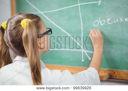 Pupil with lab coat writing on chalkboard in a classroom in school