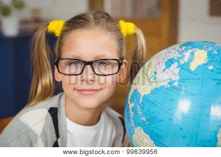 Portrait of cute pupil smiling next to globe in a classroom in school