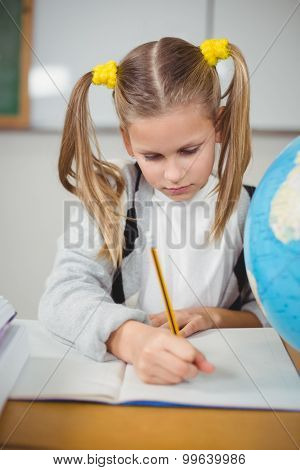 Cute pupil working at her desk in a classroom in school
