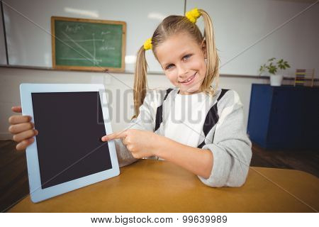Portrait of smiling pupil pointing on tablet in a classroom in school