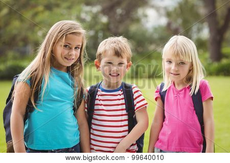 Portrait of smiling classmates with schoolbags on campus