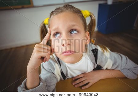 Thoughtful pupil sitting at her desk in a classroom in school
