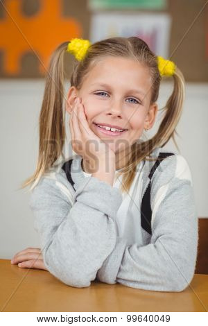 Portrait of cute pupil sitting at her desk in a classroom in school