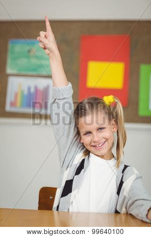 Portrait of cute pupil raising hand in a classroom in school