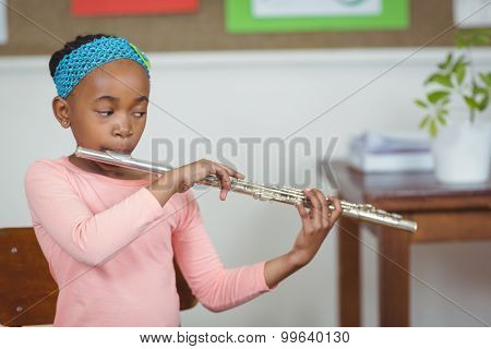 Cute pupil playing flute in a classroom in school