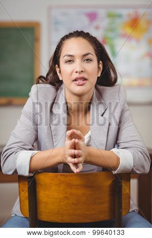 Portrait of pretty teacher sitting on chair in a classroom in school