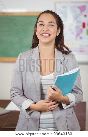 Portrait of pretty teacher holding notebook in a classroom in school