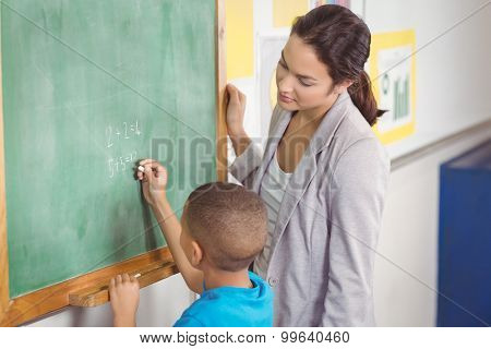 Pretty teacher helping pupil at chalkboard in a classroom