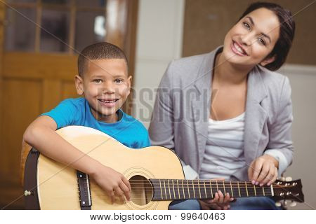 Portrait of pretty teacher giving guitar lessons to pupil in a classroom