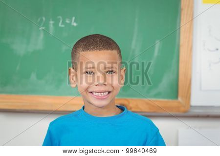 Portrait of cute pupil standing in front of chalkboard in a classroom