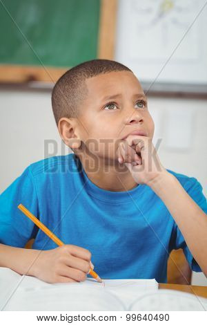Concentrated pupil working at his desk in a classroom in school