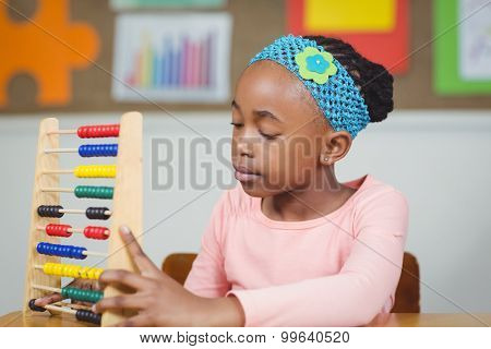 Focused pupil calculating with abacus in a classroom in school