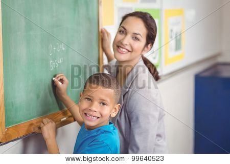 Portrait of pretty teacher helping pupil at chalkboard in a classroom