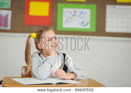 Smiling pupil daydreaming in a classroom in school
