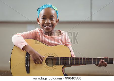Portrait of smiling pupil playing guitar in a classroom in school