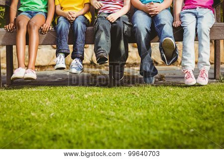 Close up view of classmates sitting on bench on campus
