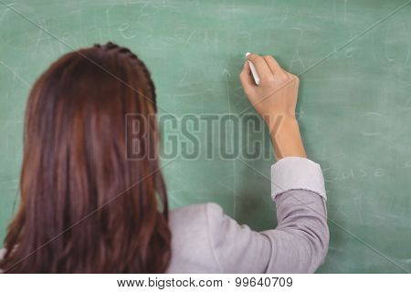 Rear view of teacher writing on chalkboard in a classroom in school