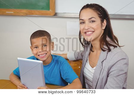 Portrait of pretty teacher and pupil with tablet at his desk in a classroom