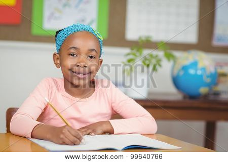 Portrait of cute pupil working at her desk in a classroom in school