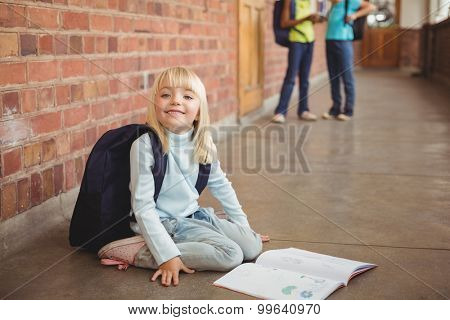 Portrait of cute pupil kneeling over notepad at corridor in school