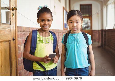 Portrait of cute pupils with smartphone at corridor in school
