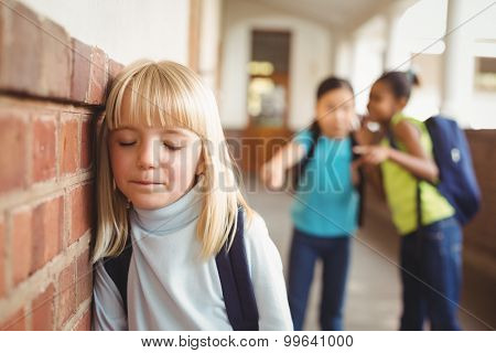 Sad pupil being bullied by classmates at corridor in school