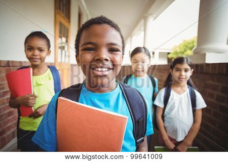 Portrait of cute pupils holding notebooks at corridor in school