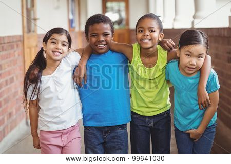 Portrait of cute pupils having arms around at corridor in school