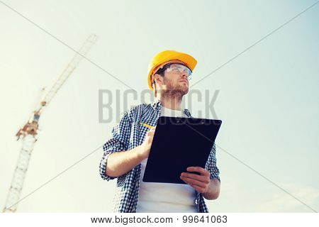 business, building, paperwork and people concept - builder in hardhat with clipboard outdoors