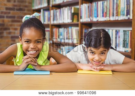 Portrait of smiling pupils leaning on books in the library in school