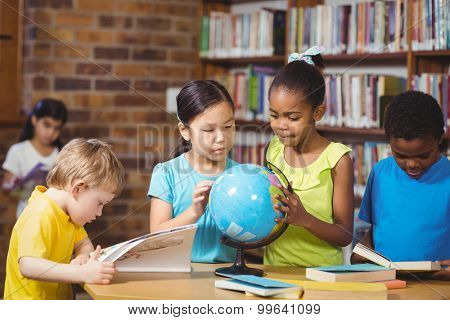 Pupils studying globe in the library in school