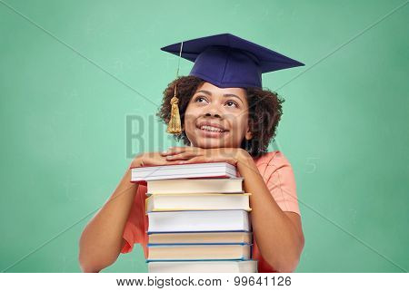 education, school, knowledge and people concept - happy smiling african american student girl in bachelor cap with books sitting at table and dreaming over green chalk board background