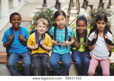 Portrait of happy pupils with schoolbags sitting on bench in school