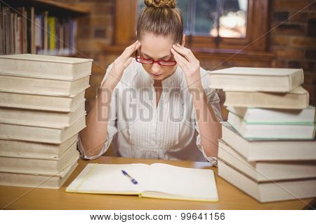 Focused blonde teacher sitting between books in the library in school