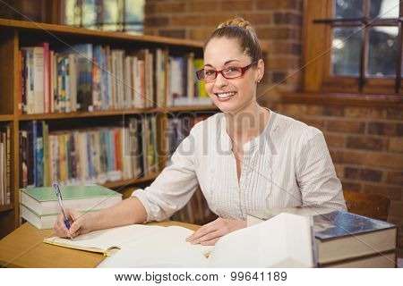Portrait of blonde teacher correcting in the library in school
