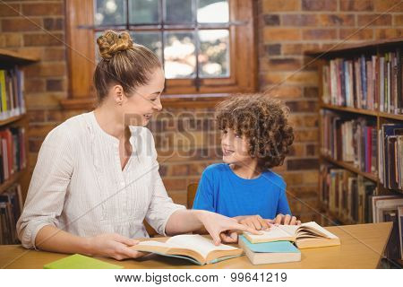Blonde teacher and pupil reading books in the library in school