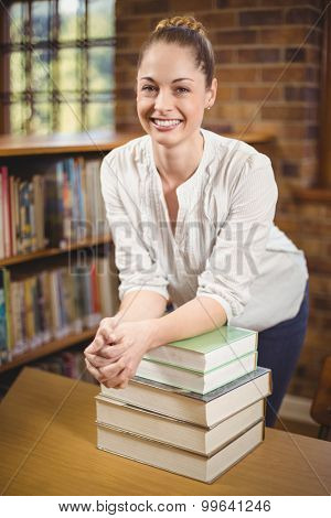Portrait of blonde teacher leaning on pile of books in the library in school