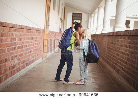 Cute pupils whispering secrets at corridor in school