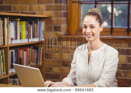 Portrait of blonde teacher using laptop in the library in school