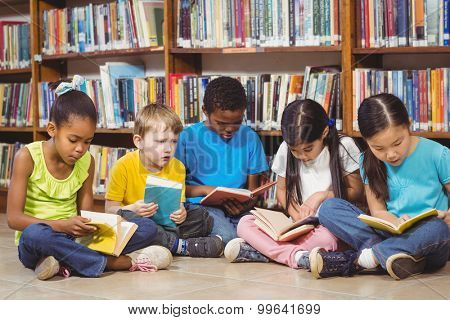 Pupils sitting on the ground and reading books in the library in school