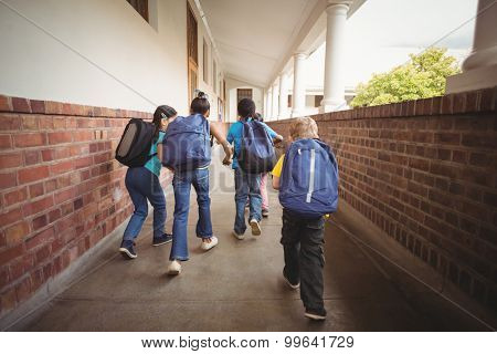 Rear view of pupils walking at corridor in school