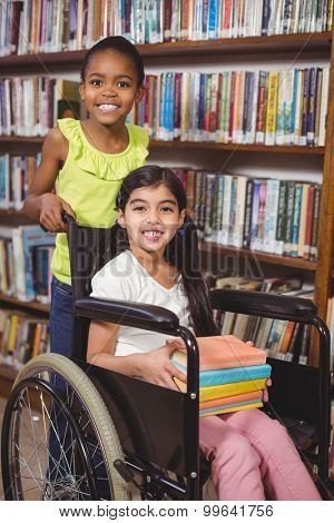 Portrait of smiling pupil in wheelchair holding books in the library in school