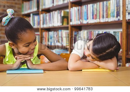 Smiling pupils leaning on books in the library in school