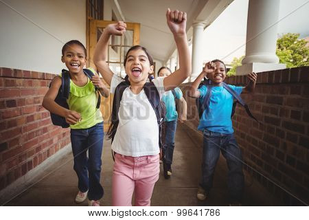 Happy pupils running around the corridor in school