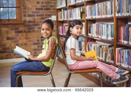 Portrait of smiling pupils reading books in the library in school